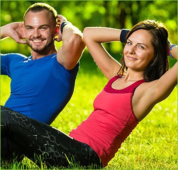 Couple Doing Situps in the Grass